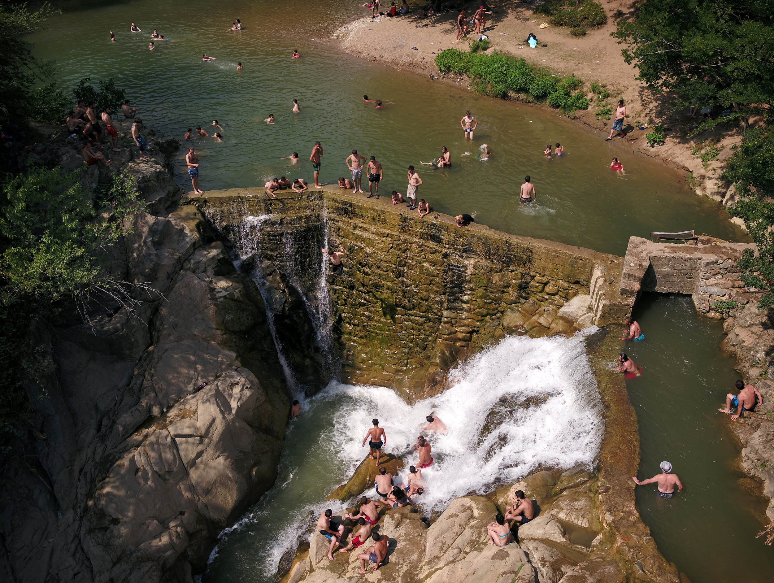 People jumping from the wall of the Samtsvera waterfall, near Zestafoni.