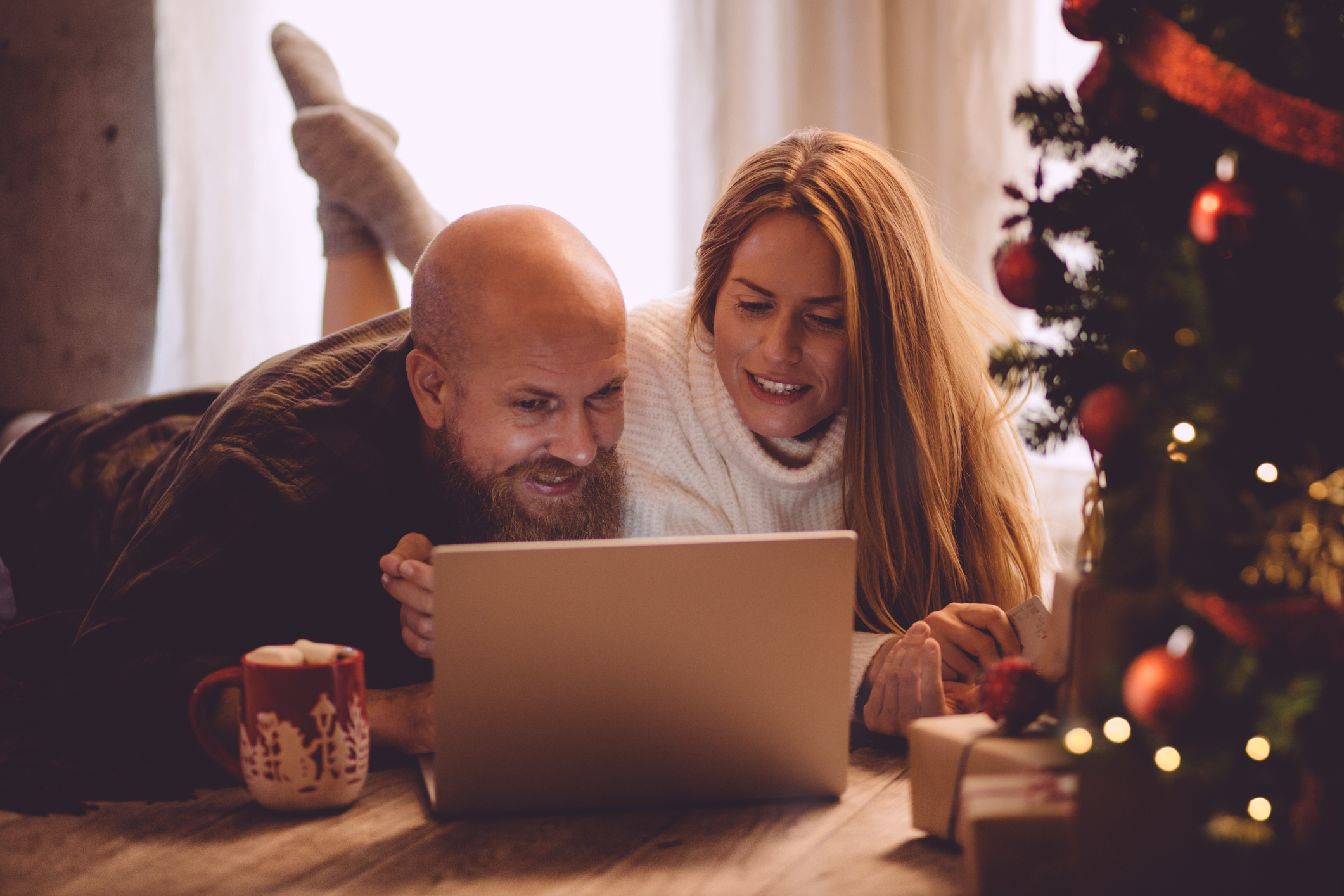 A woman and a man look at a laptop under a Christmas tree with christmas festive decorations