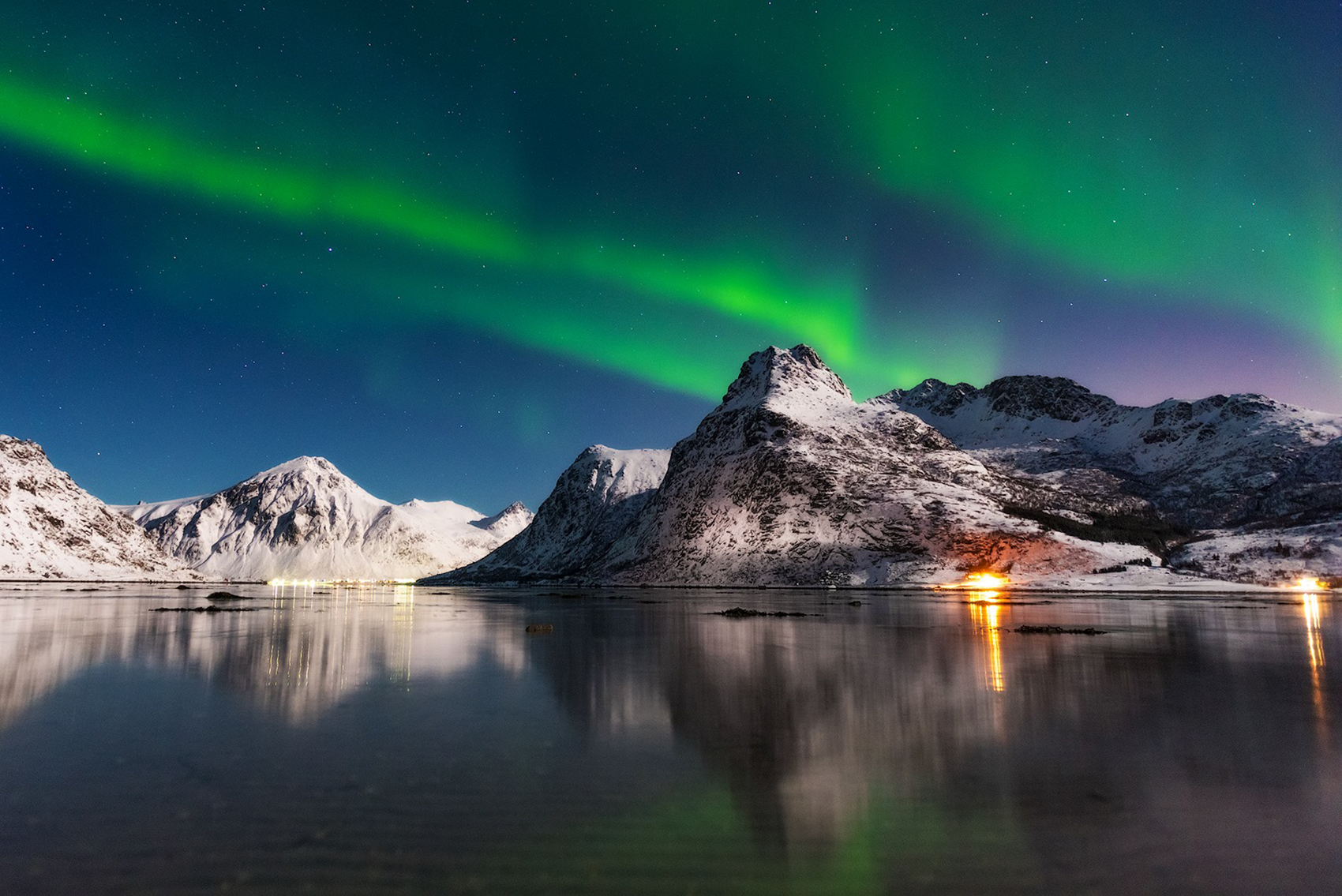 A small display of the northern lights over the Lofoten Islands of Norway during a full moon.