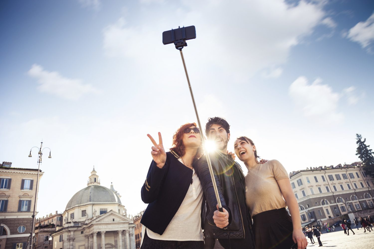 Group of happy friend spending some time together taking selfies using a selfie stick.