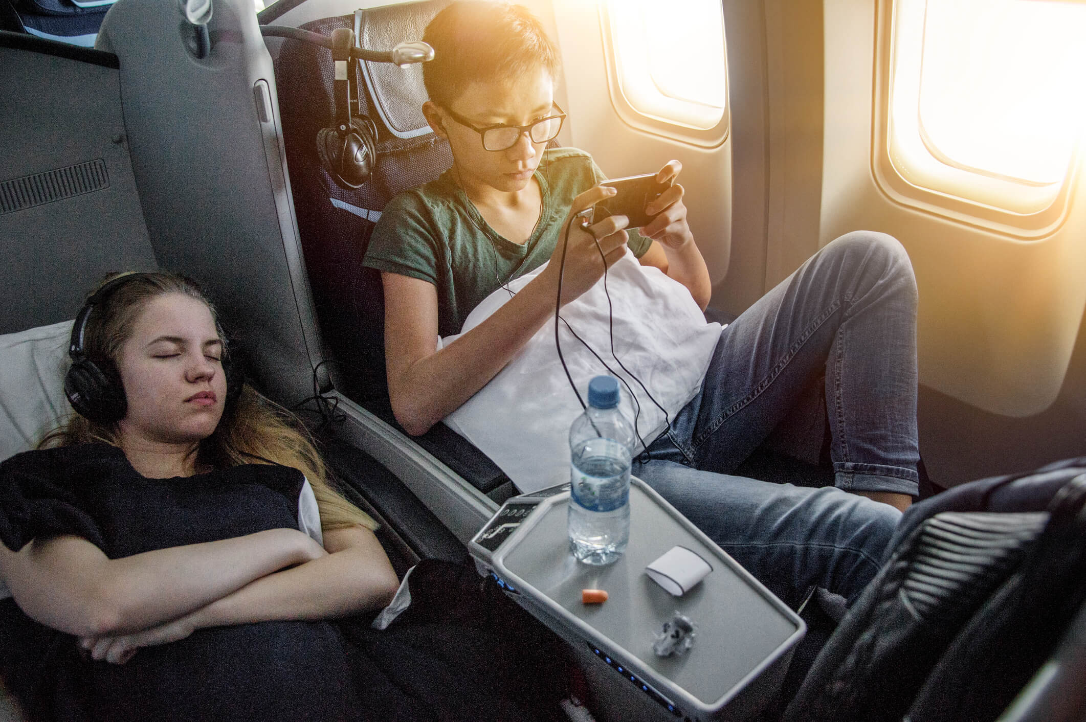 Two teenager on business class seats in airplane