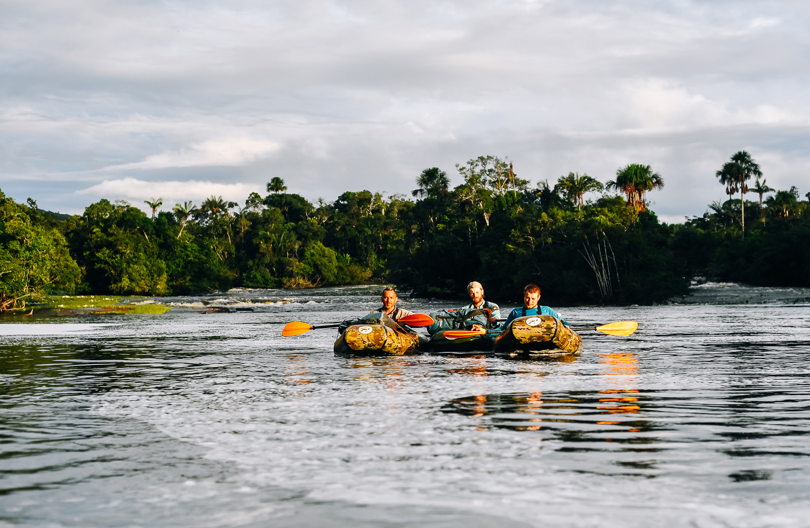 Three of the adventurers paddling on the Amazon