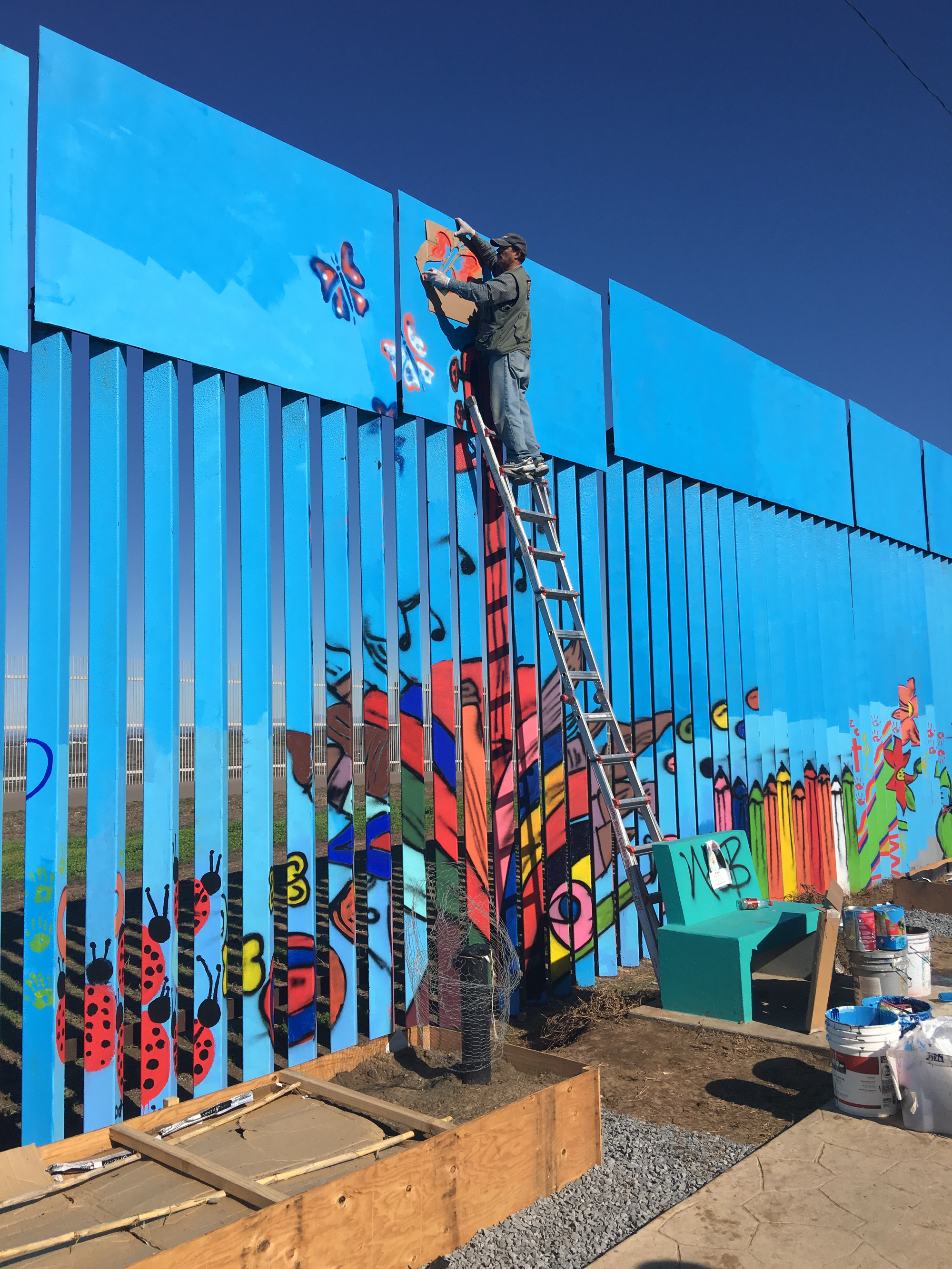 Enrique Chiu painting a section of the Mexico-US border wall.
