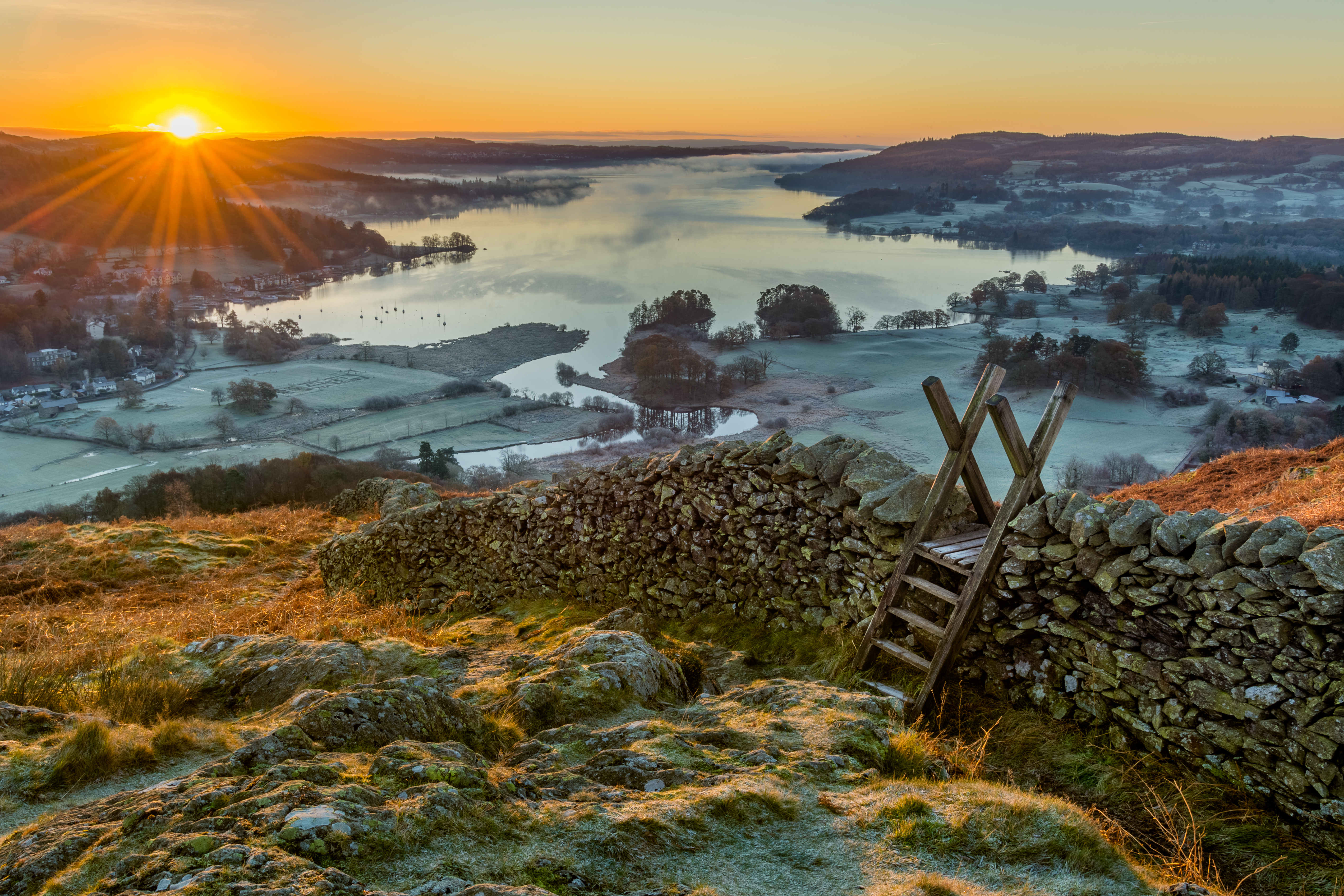 Wooden stile and stone wall with Lake Windermere in background with sun rising above horizon.