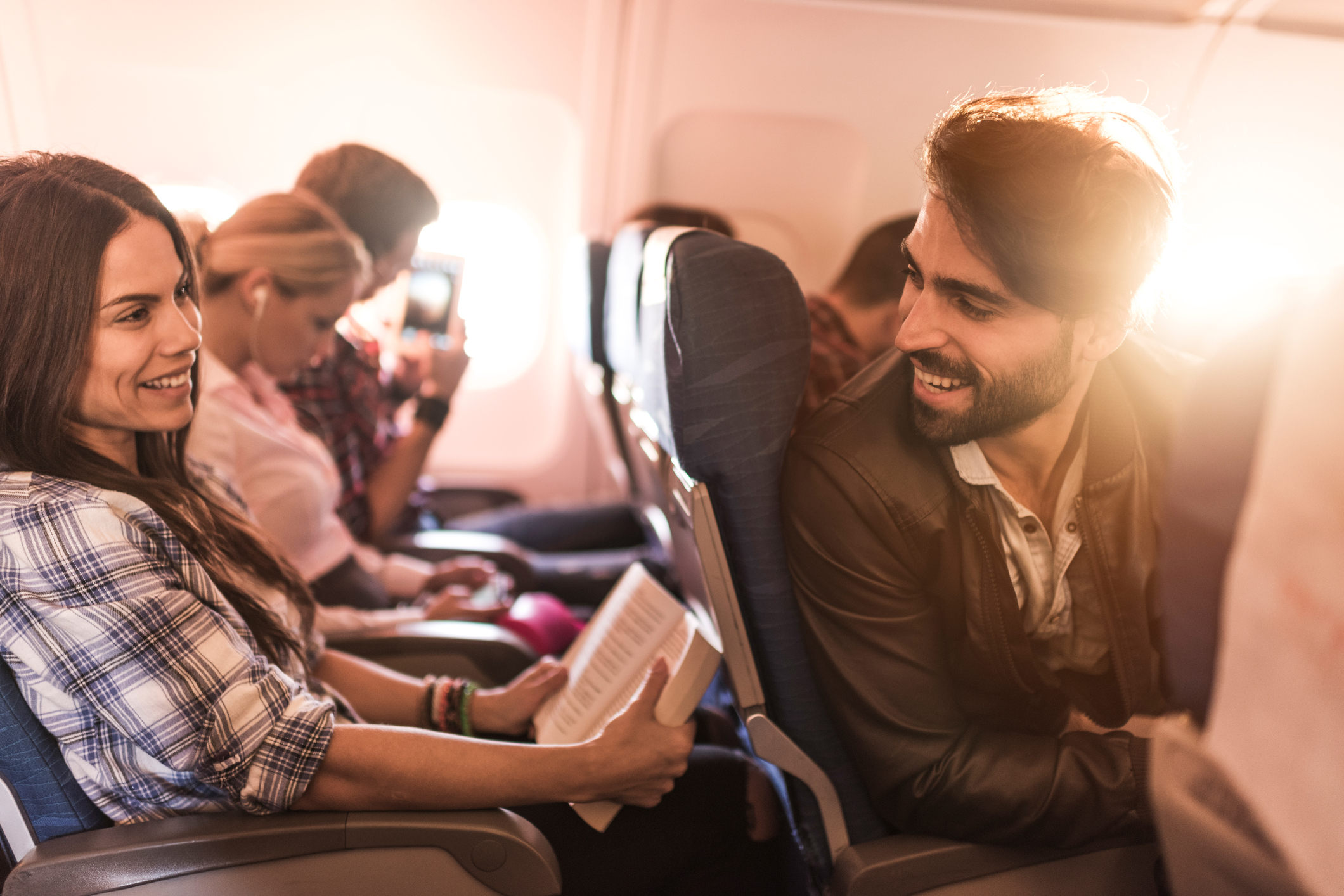Happy passengers traveling by airplane and talking to each other. Focus is on man.