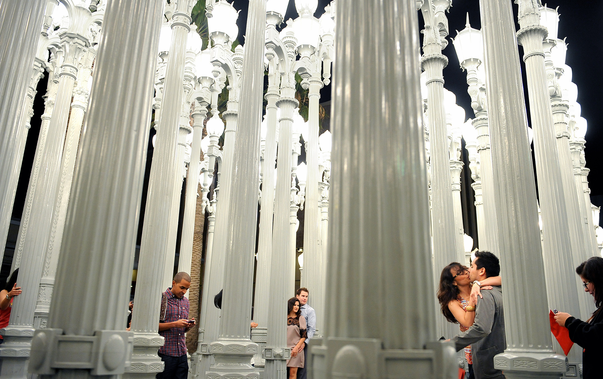 People explore the Urban Light sculpture