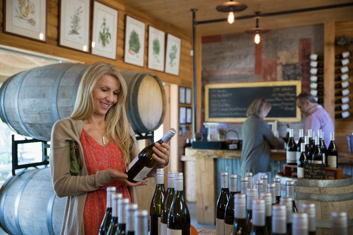 Woman shopping for wine in winery tasting room
