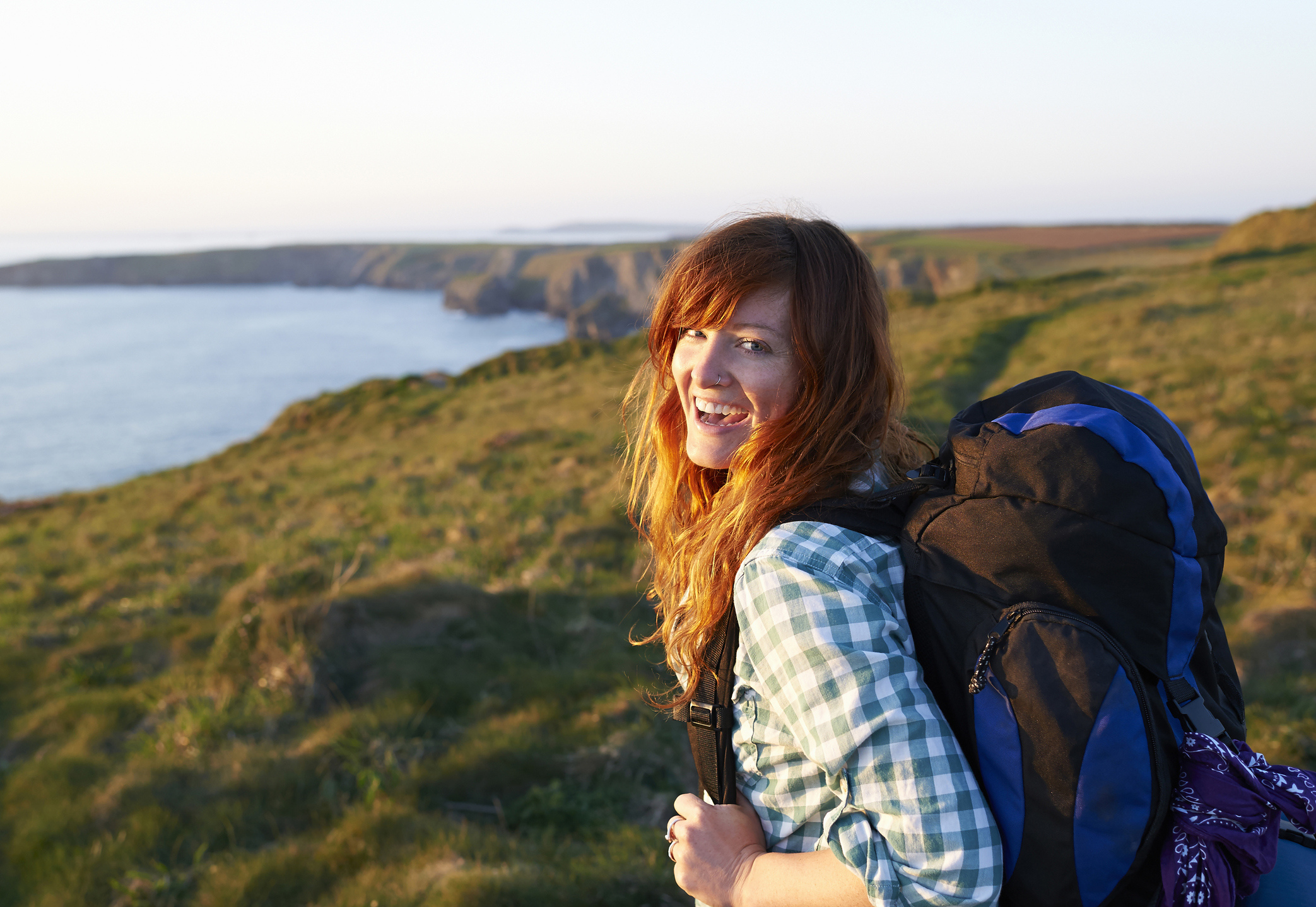 A woman walks along a coastal path.