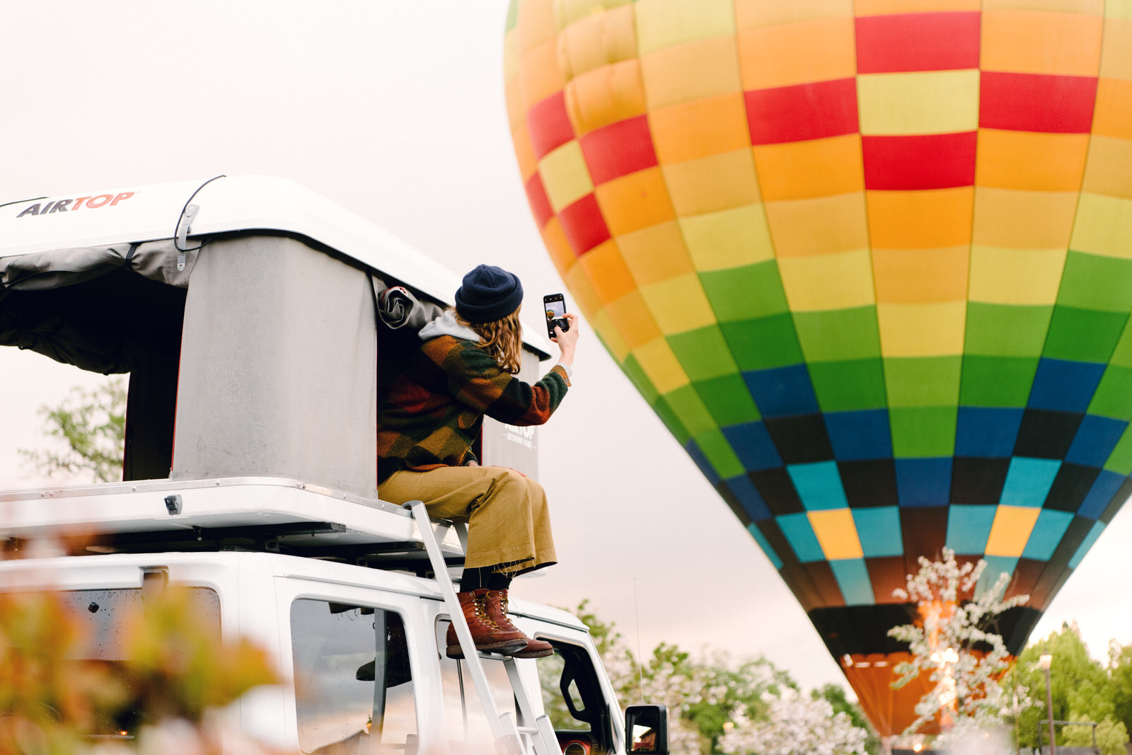 Person taking pictures of a hot air balloon out of an RV