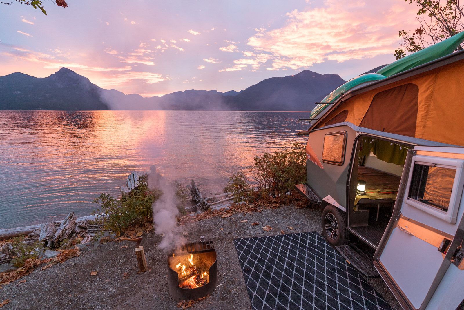 Outdoorsy RV parked by a lake at sunset